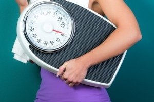 Wombourne Hypnotherapy for weight loss - fit woman with scales